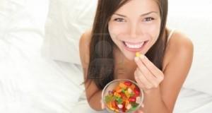 7648242-mujer-de-candy-comer-dulces-con-una-sonrisa-fresca-en-la-cama--espacio-de-copia-vista-superior-de-ch